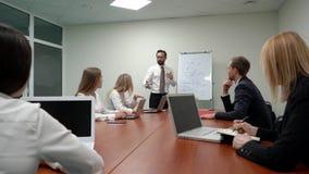 Líder do homem de negócios que explica um esquema no whiteboard à equipe nova do negócio na reunião com no escritório video estoque