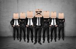 Líder e seu pessoal que ficam junto com caixas em suas cabeças fotografia de stock royalty free