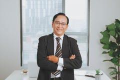 Líder empresarial asiático mayor confiado que se coloca en la oficina Foto de archivo