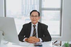 Líder empresarial asiático mayor confiado que se sienta en el escritorio Fotografía de archivo