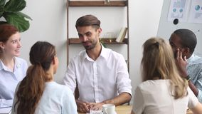Líder empresarial feliz que habla en el equipo multicultural que encuentra al empleado del apretón de manos metrajes