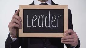 Líder escrito en la pizarra en manos del hombre de negocios, jefe del proyecto, carrera almacen de video