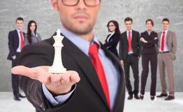 Líder de un businessteam que detiene al rey blanco del ajedrez Fotografía de archivo