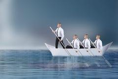 Líder Lead su Team Paddling en el barco del papel imagen de archivo