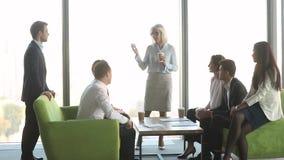 Líder maduro de sexo femenino que habla con los clientes de los trabajadores en el descanso para tomar café almacen de video