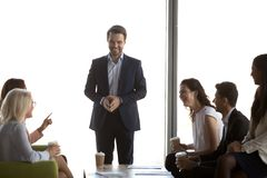 Líder masculino amigável que tem a conversação do divertimento com a equipe dos trabalhadores de escritório fotografia de stock royalty free