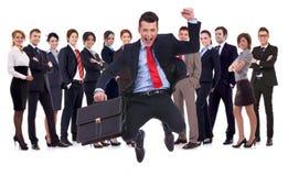 Líder novo que salta para a alegria na frente de sua equipe imagens de stock royalty free