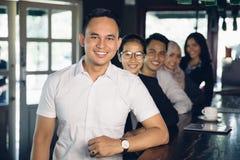 Líder ocasional do homem de negócios no primeiro plano de sua equipe Fotos de Stock