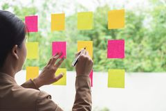 Líder profesional creativo joven usando notas de post-it en vidrio imágenes de archivo libres de regalías
