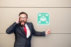 Líder profesional hermoso que señala extremadamente a la muestra del punto de reunión Encargado en traje y lazo rojo que pide enc imagenes de archivo