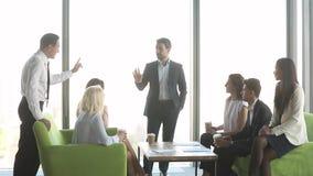 Líder que habla para combinar a los empleados que consultan al grupo de los clientes en la reunión metrajes