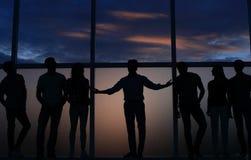 Líder y un grupo de gente joven que se coloca cerca de una ventana grande fotografía de archivo libre de regalías