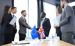 Líderes da União Europeia e do Reino Unido que agitam as mãos em um acordo do negócio Brexit fotografia de stock royalty free