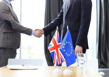 Líderes da União Europeia e do Reino Unido que agitam as mãos em um acordo do negócio Brexit imagens de stock royalty free