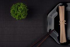 Líe los tallarines asiáticos crudos en la placa con los palillos, planta verde en fondo rayado negro de la estera con el espacio  Imagen de archivo libre de regalías