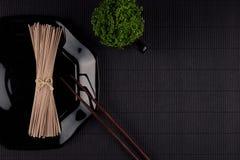 Líe los tallarines asiáticos crudos en la placa con los palillos, planta verde en fondo rayado negro de la estera con el espacio  Imágenes de archivo libres de regalías