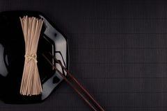 Líe los tallarines asiáticos crudos en placa con los palillos en fondo rayado negro de la estera con el espacio de la copia, visi Fotos de archivo libres de regalías