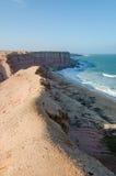 Línea áspera de la costa con los acantilados elevados y océano salvaje en Angola imagenes de archivo