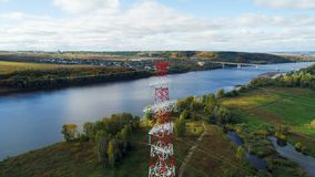 Línea aérea de alto voltaje contra el puente distante sobre el río almacen de metraje de vídeo