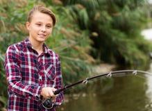 Línea alegre del bastidor del muchacho para pescar en el lago Imágenes de archivo libres de regalías
