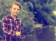 Línea alegre del bastidor del muchacho para pescar en el lago Fotografía de archivo libre de regalías