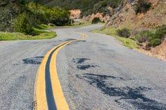 Línea amarilla doble abajo camino ventoso de la montaña Imágenes de archivo libres de regalías