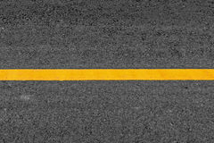 Línea amarilla en fondo del camino de la textura del asfalto con granoso imagenes de archivo