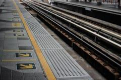 Línea amarilla y flecha con el ferrocarril en la estación del skytrain Foto de archivo