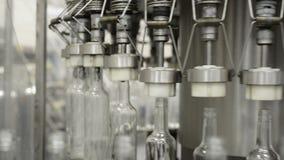 Línea automática de embotellamiento de bebidas alcohólicas El trabajo del primer mecánico de los agarradores almacen de video