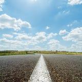 Línea blanca en la carretera de asfalto debajo del cielo con las nubes Foto de archivo libre de regalías
