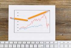 Línea condiciones del mercado reflectoras del gráfico en un escritorio de madera rústico Fotos de archivo