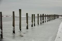 Línea continua de pilas del muelle en agua congelada Imagen de archivo
