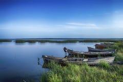 Línea de barcos en el agua colocada en los lagos bielorrusos Braslav del parque nacional en la puesta del sol durante tiempo de v Imagen de archivo