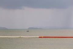 Línea de boyas anaranjadas y blancas flotantes para la zona de seguridad de marcado Fotos de archivo