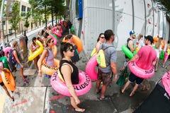 Línea de Carry Innertubes And Wait In de la gente en el evento del Waterslide Fotografía de archivo