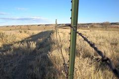 Línea de cerca del alambre de púas y cerca viejas Post Imagen de archivo libre de regalías
