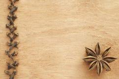 Línea de clavos, anís de estrella en una tabla de madera fotos de archivo libres de regalías