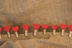 Línea de corazones en el fondo orgánico de la harpillera imagen de archivo
