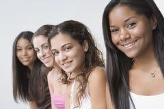 Línea de cuatro chicas jóvenes que sonríen en la cámara Foto de archivo
