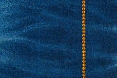 Línea de diamantes artificiales amarillos integrados en una tela del dril de algodón Con el espacio para el texto Imagen de archivo libre de regalías