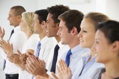 Línea de hombres de negocios felices y positivos que aplauden Fotos de archivo libres de regalías