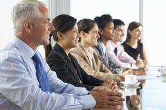 Línea de hombres de negocios que escuchan la presentación asentada en Glas imágenes de archivo libres de regalías