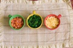 Línea de ingredientes en tazas coloridas Fotos de archivo libres de regalías