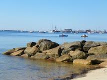 Línea de la playa del océano, embarcadero del canto rodado, barcos y kayakers del mar en backgro Fotografía de archivo libre de regalías