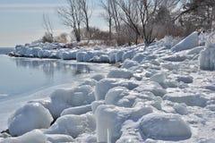 Línea de la playa encrustada hielo con reflexiones del hielo del lago Foto de archivo