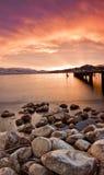 Línea de la playa rocosa en la puesta del sol en el agua Imagen de archivo