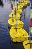 Línea de pequeños barcos amarillos en el agua Fotos de archivo