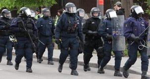 Línea de policía antidisturbios que marcha a continuación mientras que bastón táctico en su escudo metrajes