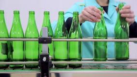 Línea de producción del agua El empleado pone las botellas de cristal en la línea de botellas automáticas de la limpieza y del re almacen de video