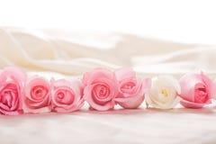 Línea de rosas rosadas y blancas que ponen en el backgr de seda Fotografía de archivo